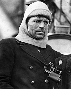 Unshaven man in heavy clothing and holding a pair of binoculars