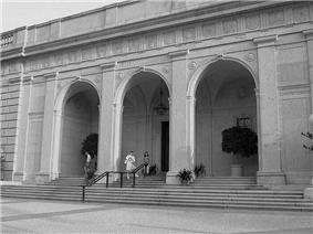 The entrance to a one story stone Beaux Arts style building. It consists of three large arches with stairs going up to and through them. The entrance door sits behind the middle arch.