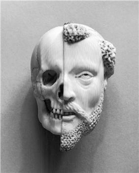 Ivory pendant of a Monk's face. The left half of the pendant appears skeletal, while the right half appears living