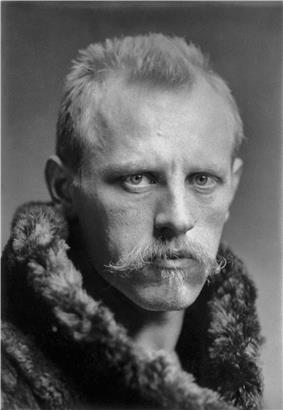 Head of a man with a determined expression, blond hair and moustache, looking straight to the camera