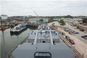Looking down the front of a ship towards the yard, with artillery guns in the foreground and the buildings of the yard in the background