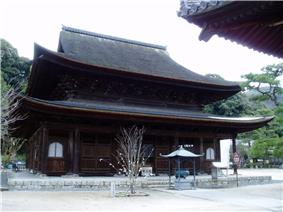 Large wooden building with a hip-and-gable roof and an enclosing pent roof.