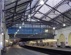 The interior of a building with white walls, white flooring, and a railway track running down the middle of the corridor with a train on it