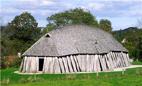 A primitive one-storey hut made of wooden planks with shingled roof, a single entrance and a few small skylights.
