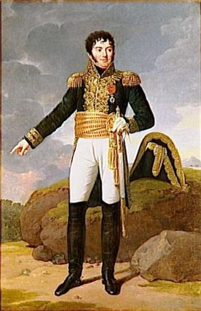 Formal full-length portrait of a Tharreau in uniform, in a rocky landscape. He is a short, solidly built man with a round face and alert dark eyes. His pale skin contrasts with his black curly hair and heavy cheek whiskers. He looks out of the picture to the left while gesturing backward with his right hand. He holds a sword in his left hand.