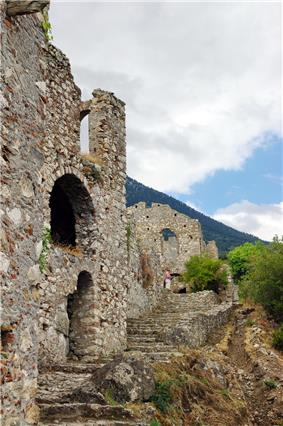 A complex of buildings partially in ruins in a mountain landscape.