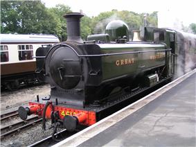 A green pannier tank locomotive standing at a platform with a red passenger carriage behind. The lettering