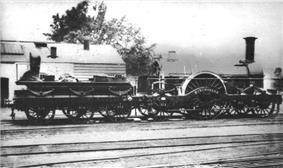 A black and white image showing a steam locomotive facing to the right. The low tender on the left has six wheels; the engine itself has a large wheel in the middle with two wheels in front and one behind.