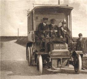 A sepia picture of an old bus, seen from the front. The cab is open to the elements and three men sit in it, while a boy stands to the right.