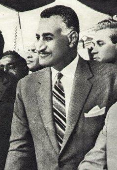 A smiling man with a black mustache faces the viewer's left. His hair is dark and short, white at the temples. He is wearing a western-style two-piece gray suit and white shirt, with an angularly striped tie and visible white pocket handkerchief. Behind him several faces are visible.