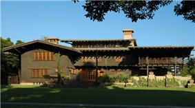 Photograph of the David B. Gamble House across its front lawn. It is a large house with wooden siding and trim presenting a very rustic feel.