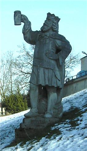A proud statue of Gambrinus looking up at a mug of beer he holds with one hand; his other hand rests on his hip. Snow surrounds the statue.