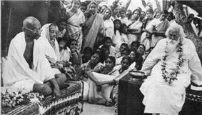 Photo of a formal function, an aged bald man and old woman in simple white robes are seated side-by-side with legs folded on a rug-strewn dais; the man looks at a bearded and garlanded old man seated on another dais at left. In the foreground, various ceremonial objects are arrayed; in the background, dozens of other people observe.