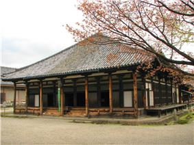 Wooden building with pyramid shaped roof and white walls.