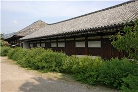 Long wooden building with white walls.