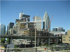 Several skyscraper buildings in background with elevated highway passing in front