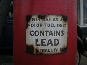 a closeup of a red gasoline pump with a warning label that reads,