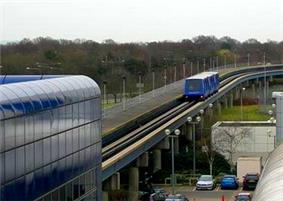 Blue, three-car train approaching a station