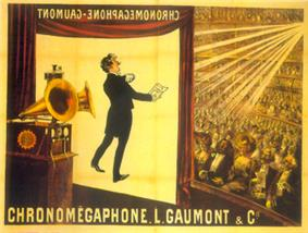 Illustration of a theater from the rear right of the stage. At the front of the stage a screen hangs down with the projected image of a tuxedoed man holding up a text and performing. In the foreground is a gramophone with two horns. In the background, a large audience is seated at orchestra level and on several balconies. The words