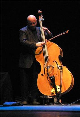 A bald white man stands playing the double bass in front of a low microphone.