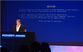 Gabe Newell stands at a podium in front of a large screen. The screen is blue, similar to the