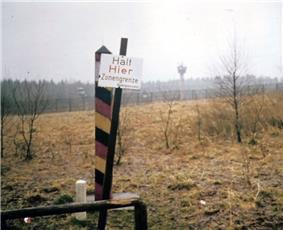 View across a landscape with a leaning sign reading
