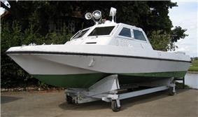 View of a small streamlined boat resting in a cradle out of the water. The boat is painted white and green, with