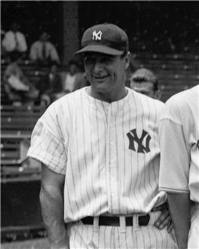 A smiling man in a dark cap and white pinstriped baseball uniform with an interlocked