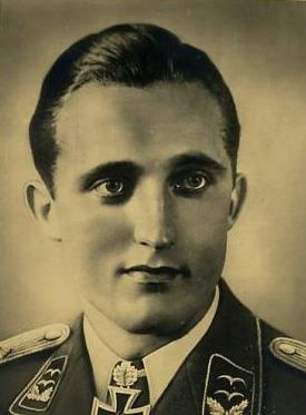 The head and shoulders of a young man, shown in semi-profile. He wears a military uniform with an Iron Cross displayed at the front of his white shirt collar. His hair appears dark, short and combed back, his nose is long and straight, and his facial expression is emotionless; looking to the left of the camera.