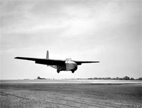 A large, bulky glider with long wings in flight, coming in to land on a runway. It is casting a shadow to its right on the runway. Fields can be seen behind it, and there are trees and bushes in the background.