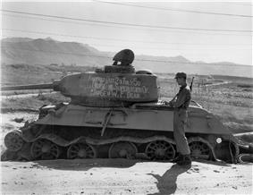 Soldiers stand around a destroyed tank with writing on it reading