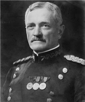 Man facing forward in uniform with two vertical columns of buttons with medals