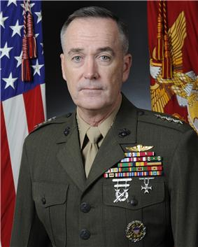 A color image of Joseph Dunford, a white male in his Marine Corps Service A uniform. He is not wearing a hat, several ribbons are visible as well as a rifle and pistol marksmanship badges and naval parachutist insignia. The Marine Corps flag and United States flag are visible in the background.
