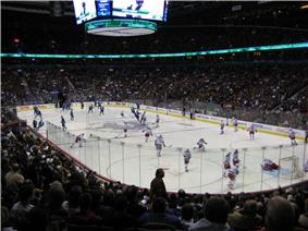 Slightly elevated view of an active ice rink. Players on one team wear mostly red and white uniforms, while the others are outfitted predominately in blue.