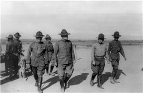 Three men in military uniform in the foreground, dressed in U.S. Army Uniforms appropriate for 1916.