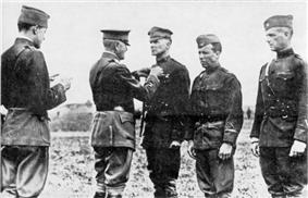 Three men in uniform are standing side by side. The one on the left is wearing a peaked