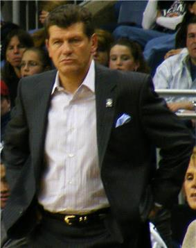 Half-length shot of a man. He is wearing an open sports coat with a white shirt underneath.