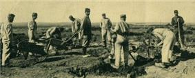 A party of German prisoners works the ground with picks under the supervision of a French guards