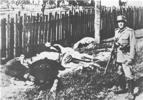 black and white photograph of several corpses in civilian clothes lying on the ground, with a male in German uniform standing near them