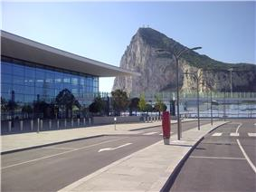 View of a modern glass—fronted building with a roadway in the foreground and the Rock of Gibraltar visible in the background
