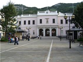 A long plaza with a large two—storey pink building at the far end, with a flight of steps leading up to the building's triple—arched entrance framed with columns.