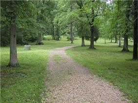 A gravel path runs across grass dotted with trees