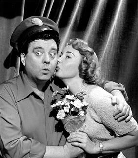 Alice Kramden kissing Ralph after he gives her a bouquet