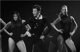 The grayscale picture of three people, two women and a man, who dance and put their hands on their hips. The man wears a dark outfit, compound of a vest, a shirt and pants. The women wear similar leotards.