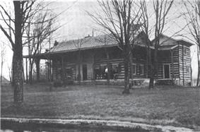 A house of wooden construction with a wrap-around front porch and trees in the front yard