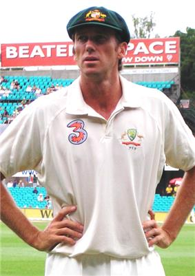 A white cricketer in cricket whites, wearing a baggy green cap. He has his hands on his hips and he is looking to his right.  He is standing in front of a bleacher.
