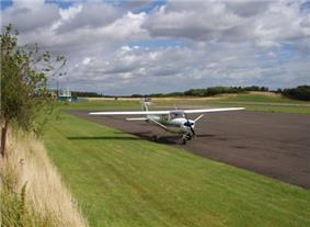 A tarmac runway is shown in the background. A small single engine plane is parked in the forecourt