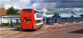 A bus concourse with bus station building to the left. The bus station has blue cladding and glass and a lantern feature on the roof with a clock and windvane