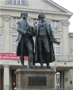 Photograph of a large bronze statue of two men standing hand-in-hand, side-by-side and facing forward. The statue is on a stone pedestal, which has a plaque that reads