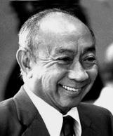 Black and white photograph of the head and shoulders of a balding Chinese man in a suit and tie, smiling broadly